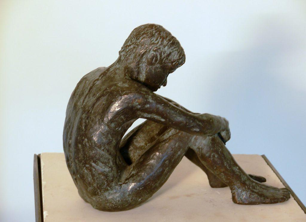 G.J. zittend met handen om knieen